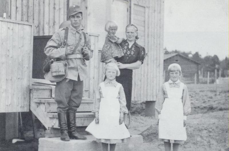 Ruotsalaistalon rappusilla Keuruun Pappilanniemessä 18.6.1941. Väinö Uosukainen lähdössä jatkosotaan. Saattamassa Leena-vaimo sylissään Ritva, edessä Raili ja Kyllikki. Takana näkyy vanhan riihen pääty. Keuruun rautatieasema jää kuvasta oikealle.