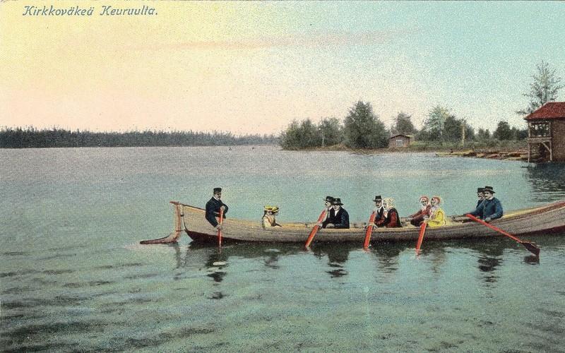 Kirkkoväkeä kirkkoveneessä soutamassa tyyntä kesäistä järven pintaa.