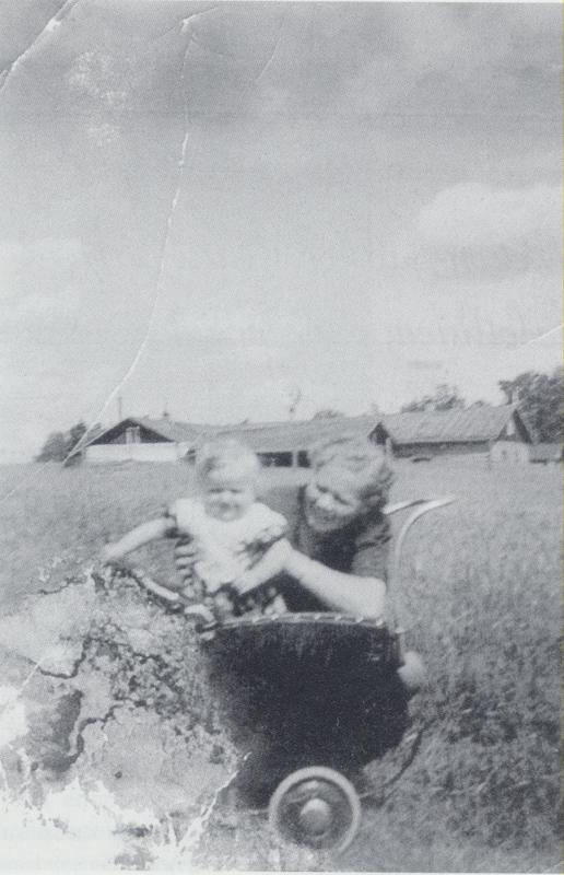 Leena Uosukainen pienokaisensa Sirpan kanssa Pappilanniemessä kesällä 1941. Taustalla pappilan navetta ja sen takana näkyy Keuruun vanhan kirkon tornia.